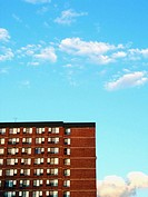 A quarter of a New York City apartment building shot against an extremely blue sky. Lots of windows, lots of blue, great clouds. USA