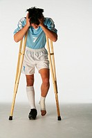 Injured soccer player using crutches