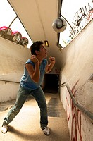 Teenage boy heading ball in underpass