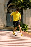 Teenage boy dribbling soccer ball in town