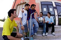 Group of teenage soccer friends on steps