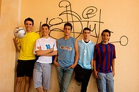 Group of teenage soccer friends against wall