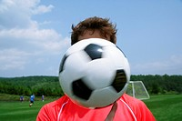 Soccer player's face obscured by ball