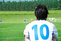 Back of soccer player watching game from side