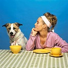 Woman watching dog at table