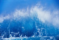 Blue waves crashing on the shore with blue sky background