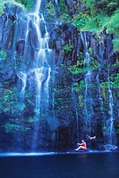 Hawaii, Maui, Hana Coast, woman sits at base of waterfall enjoying Blue Pool.