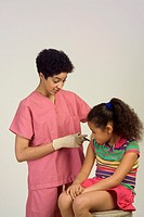 Female nurse giving a flu vaccination to a young female patient.