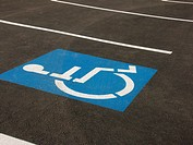 Photograph of the handicapped symbol in a handicapped designated parking space.