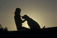 Young woman petting her dog in an idyllic setting at sunset.