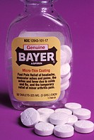 Close-up of aspirin tablets and bottle.