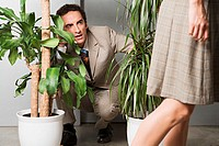 Man hiding in plants and watching woman