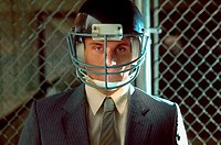 Businessman wearing american football helmet