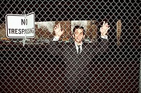 Businessman trapped behind fence