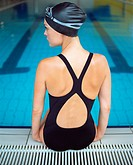 Female swimmer sitting on edge of pool