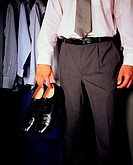 Man holding a pair of shoes (thumbnail)