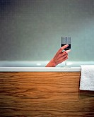 Woman holding wine glass in bath