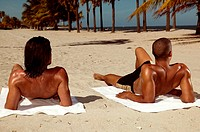 Men sunbathing on beach