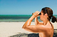 Man on beach looking through binoculars (thumbnail)