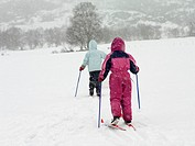 Girls on skis trekking through the snow
