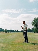 Golfer looking at his mobile phone