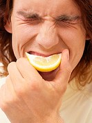 Man biting a slice of lemon