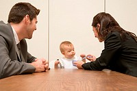 Parents feeding baby in board room