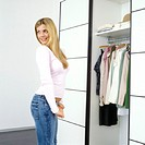 blonde woman in front of wardrobe looking over her shoulder