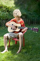 Young blond haired boy in bright red and yellow shirt playing a guitar outdoors