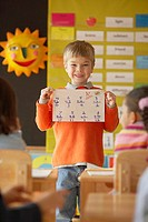 Boy holding paper up in front of class