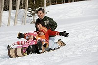 Family sledding down hill together