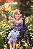 Girl in wheelchair with bouquet of flowers outdoors (thumbnail)