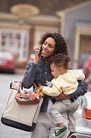 Mother carrying child talking on mobile phone