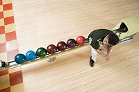 High angle view of man sitting by bowling balls
