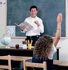 School girl raising her hand in class