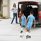 Brothers playing soccer in driveway