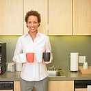 Portrait of businesswoman carrying coffee cups