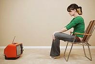 Side view of teenage girl watching TV