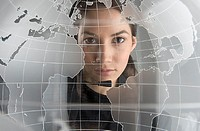 Portrait of woman looking through glass globe