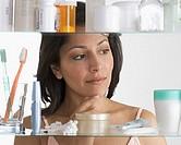 Young woman examining medicine cabinet