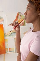 Profile of woman holding paint brush in mouth