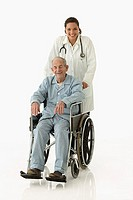 Portrait of female doctor pushing wheelchair for elderly male patient