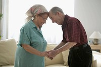 Senior couple holding hands in living room