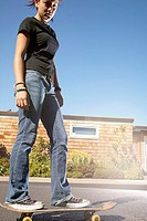 Low angle portrait of teenage girl on skateboard