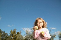 Portrait of young girl holding apples