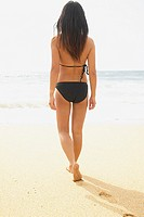 Rear view of woman walking on beach