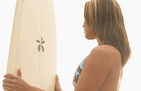 Side view of woman holding surf board