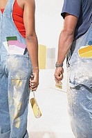 Rear view of couple with paint samples in pockets