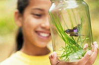 Girl looks at butterfly captured in jar