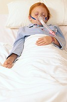 Child in a hospital bed with respirator